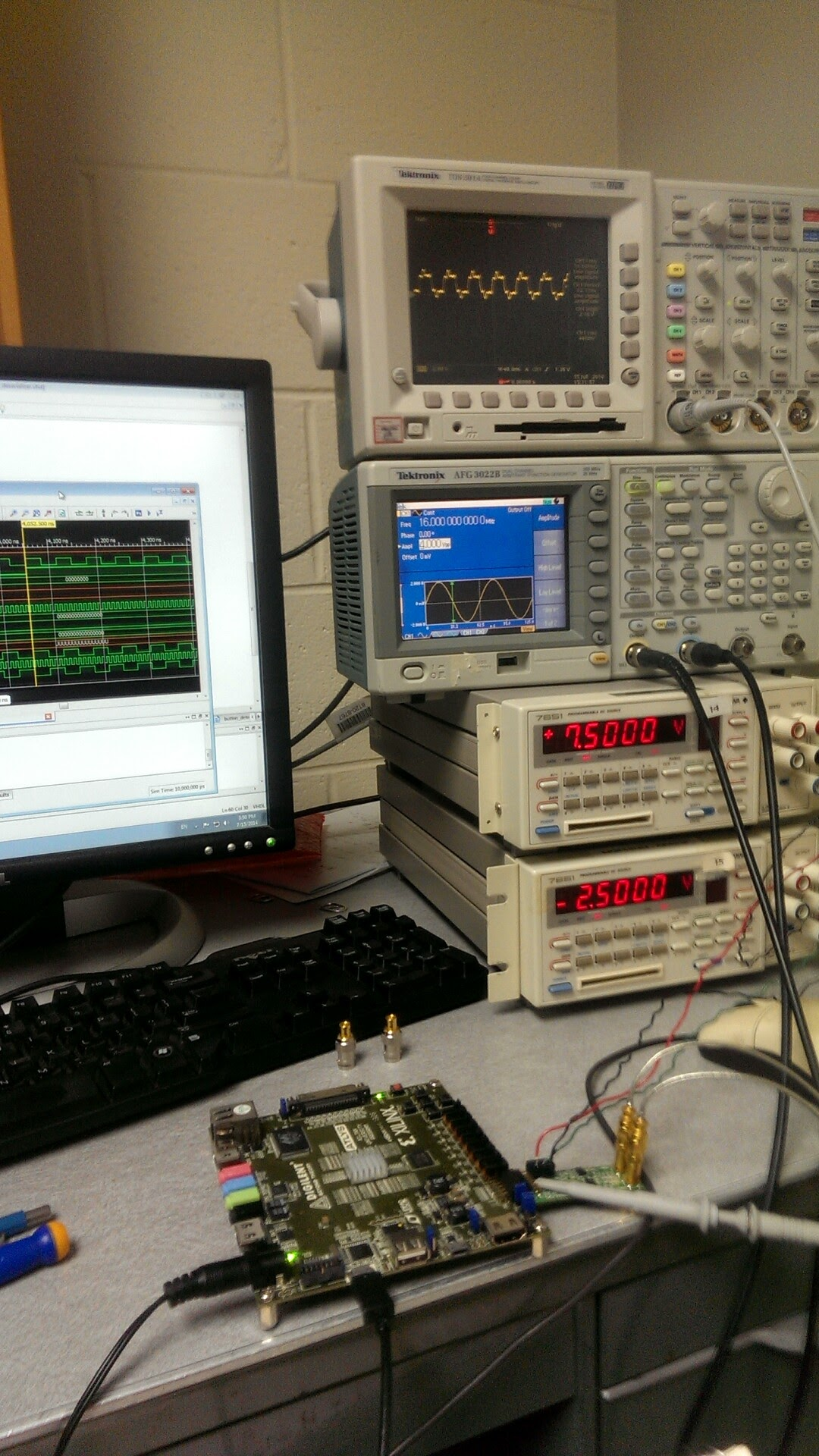 FPGA in the foreground, with a signal generator, oscilliscope, and voltage source in the background. Computer screen in the background displaying VHDL synthesis results.